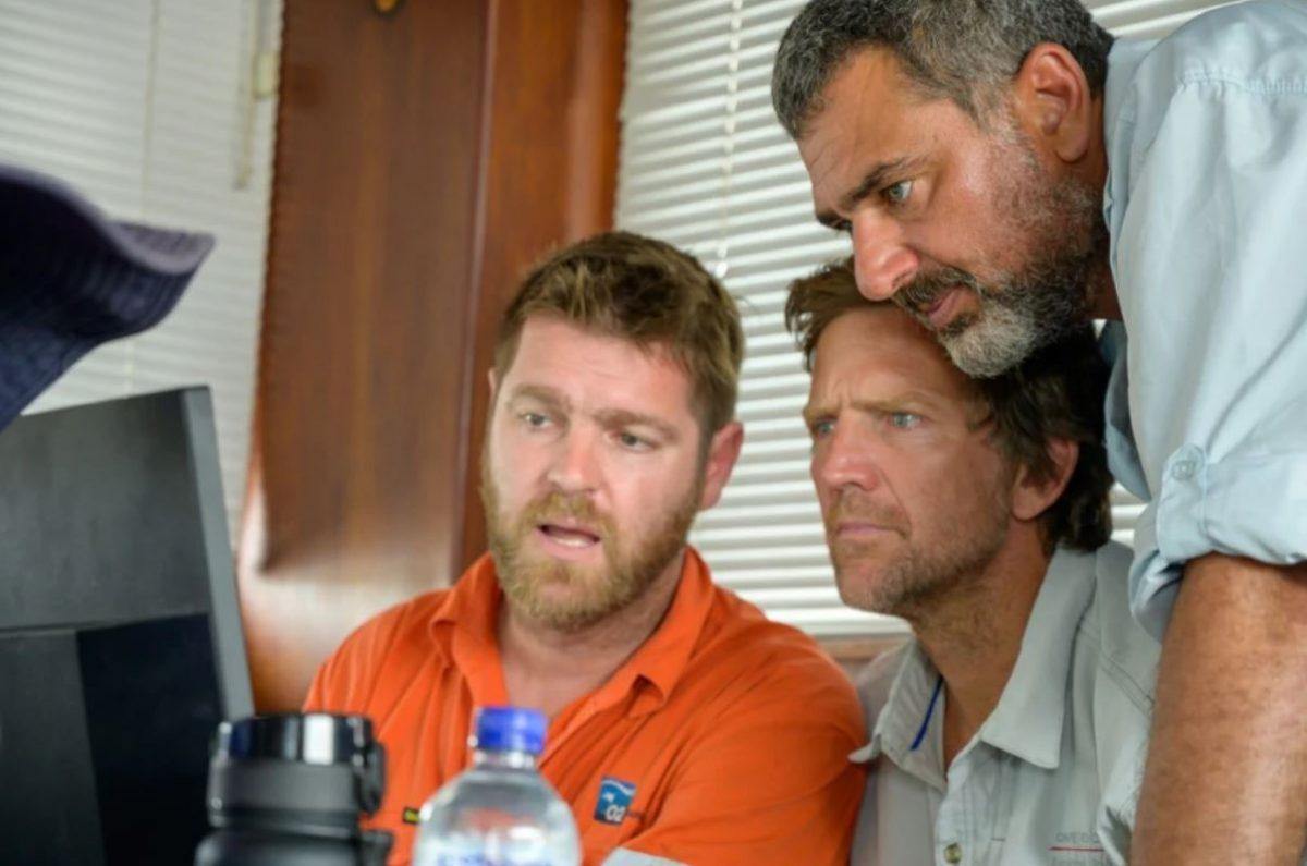 three guys looking at a computer