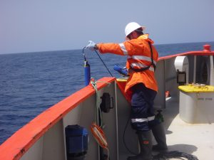 man deploying water logger over the side of a boat